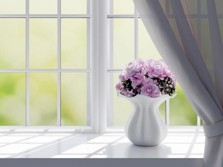 Bouquet of pink flowers (roses) on a windowsill.